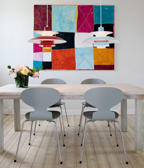White chairs and a neutral table makes this bright and colorful art stand out