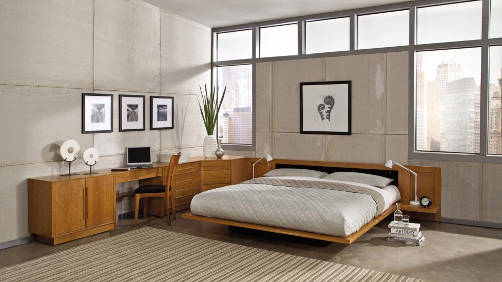 A wooden flaoting bed frame and industrial walls provide a strong contrast in materials