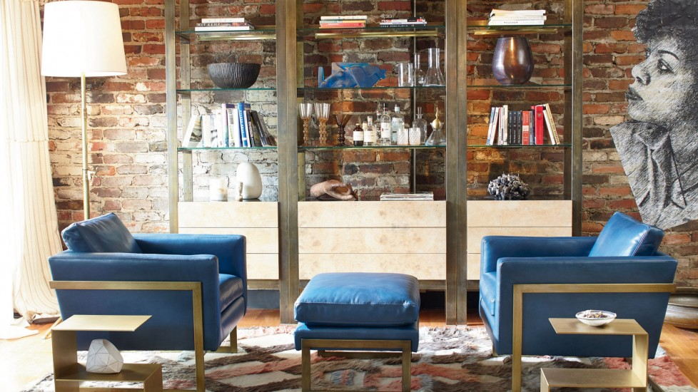 Old loft with exposed brick contrasts the clean straight lines in the blue chairs