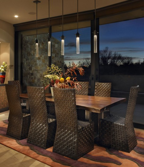 Large woven chairs and long, sleek light fixtures contrast around an all-wood dining table