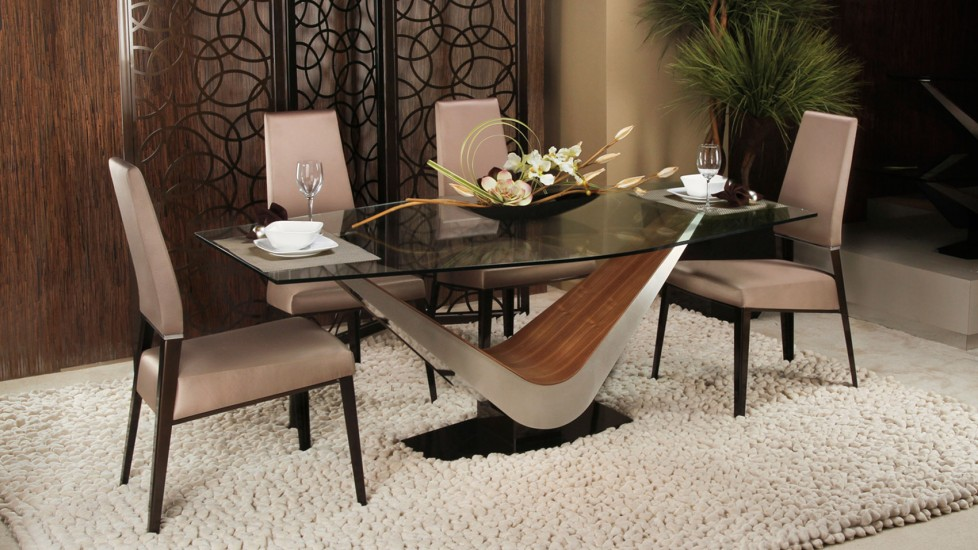 A glass top dining room table and v-style legs sink into a plush rug