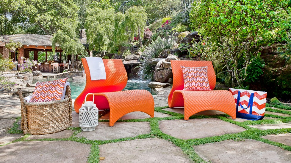 Bright orange woven chairs stand out in any outdoor setting against deep greens