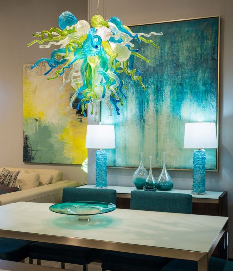 Light blue and green stained glass chandelier sheds soft tones across the dining room
