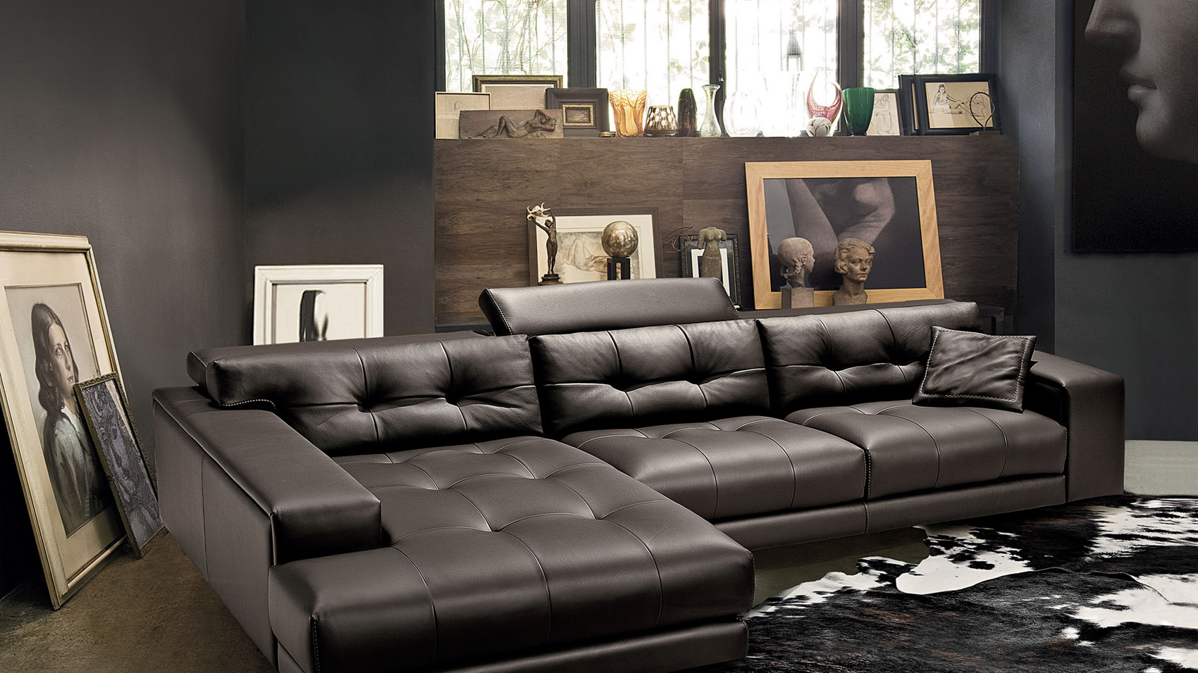 A Dark Brown Leather Couch In A Dark Room Gives A Rich, High Style Feel