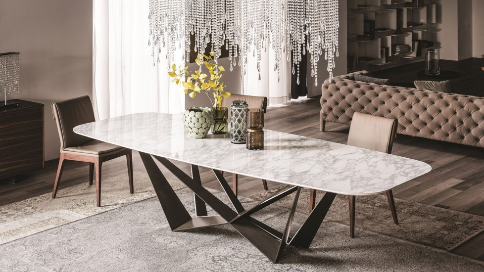 A dining room table with a marble tabletop and intricate legs in a sepia-toned dining room