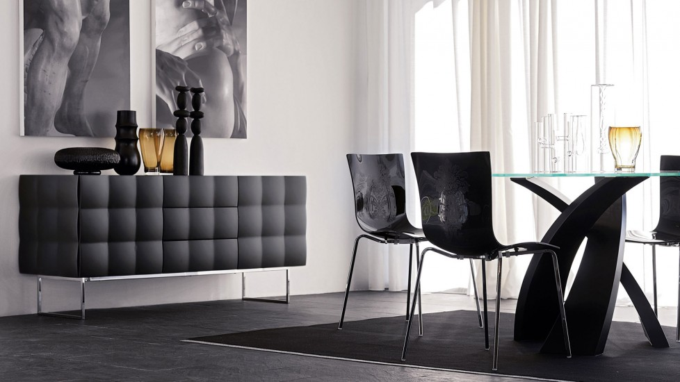 Textured black chairs and storage unit gives the white walls great contrast