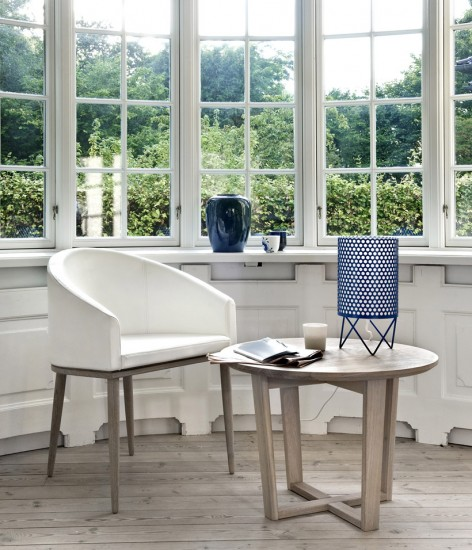 Small white chair and a end table provide the perfect reading nook beside large windows