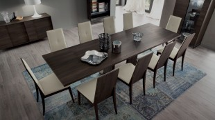 A long dark wood grain dining room table withe beige fabric chairs