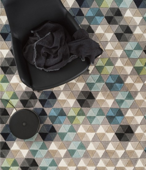 Mosaic-styled indoor rug under a black fabric chair